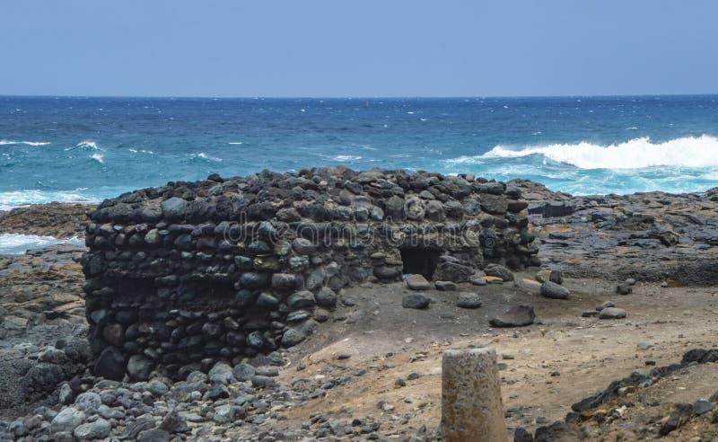 Stary prosty kamienny bunkieru dom na skalistej plaży z fala przy dniem w lecie zdjęcie stock