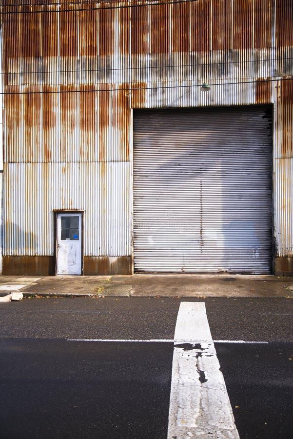 Stary przemysłowy budynek z ośniedziałą skorupą i dużą bramą fotografia royalty free
