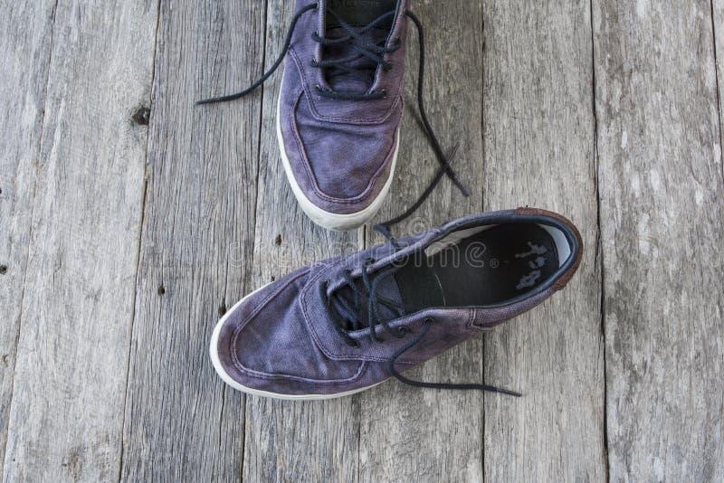 Stary przypadkowy blaknie błękitnych buty z shoelace na drewnianym tle zdjęcie stock
