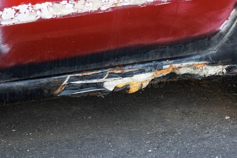 Stary, rdzawy próg czerwonego samochodu fotografia stock