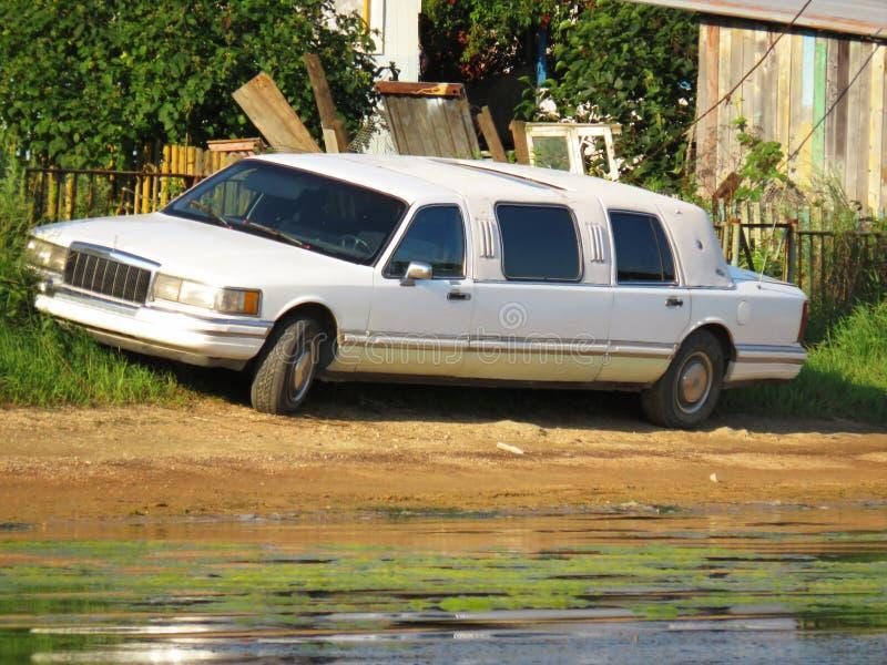 Stary retro limuzyna samochód parkował blisko chałup w krzakach na plażowym zbliżeniu zdjęcia stock