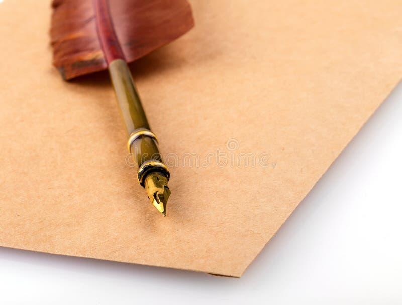 Stary rocznik palił koperta list z dutki piórka piórem na białym tle zdjęcia royalty free