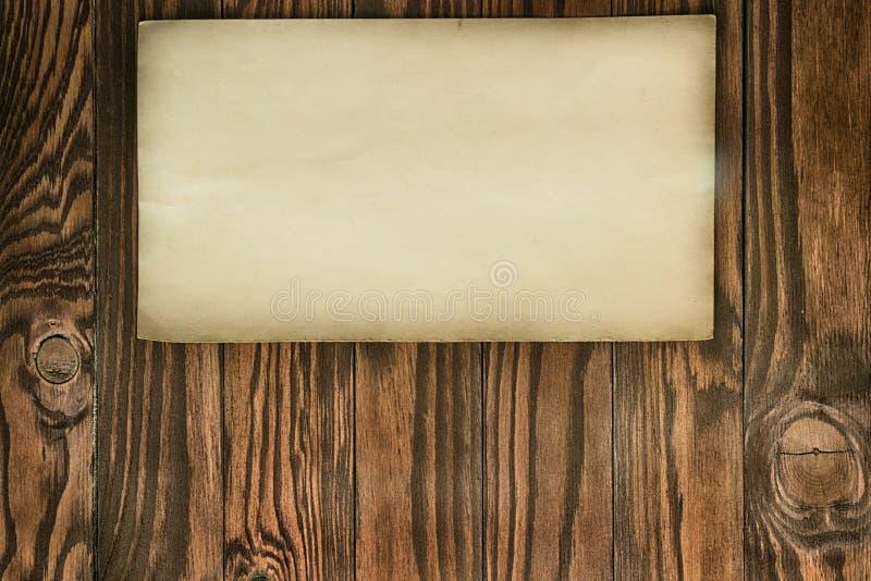 Stary rocznika papier z Poszarpaną krawędzią na Brown Drewnianych deskach obrazy royalty free