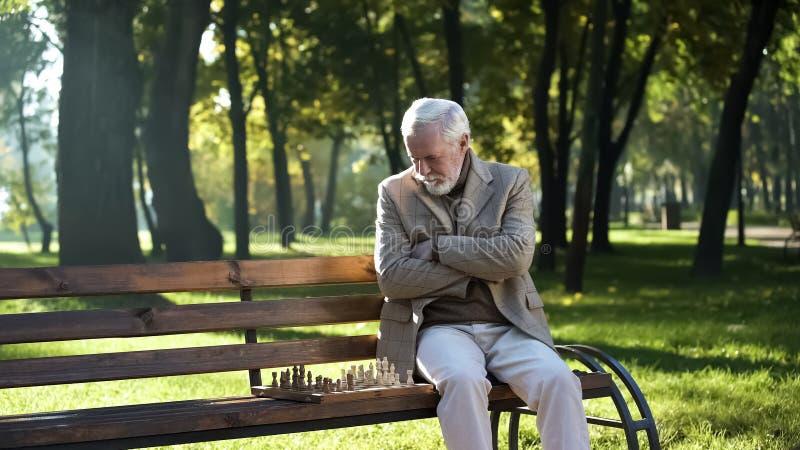 Stary rozwa?ny m??czyzna bawi? si? szachy w parkowy samotnym, ubezpieczenie spo?eczne dla emeryt zdjęcie royalty free