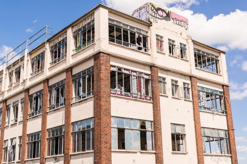 Stary, rujnujący i rujnujący przemysłowy budynek z łamanymi okno, zdjęcie stock