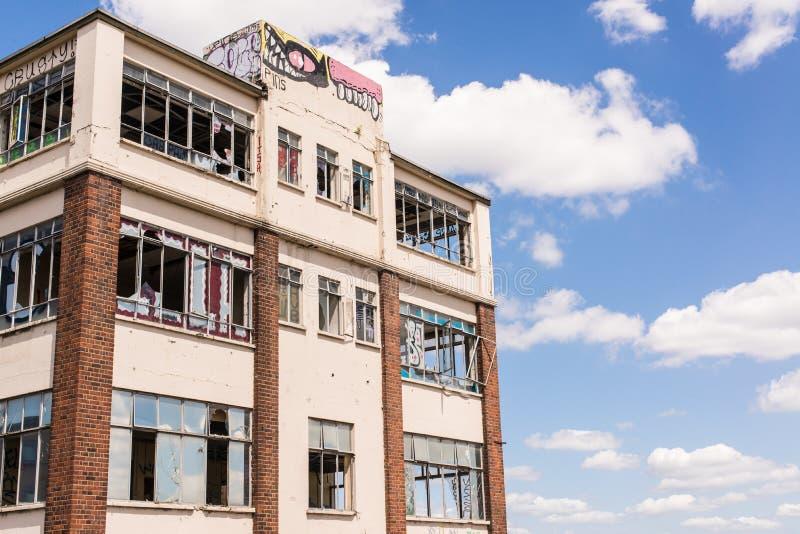 Stary, rujnujący i rujnujący przemysłowy budynek z łamanymi okno, zdjęcie royalty free