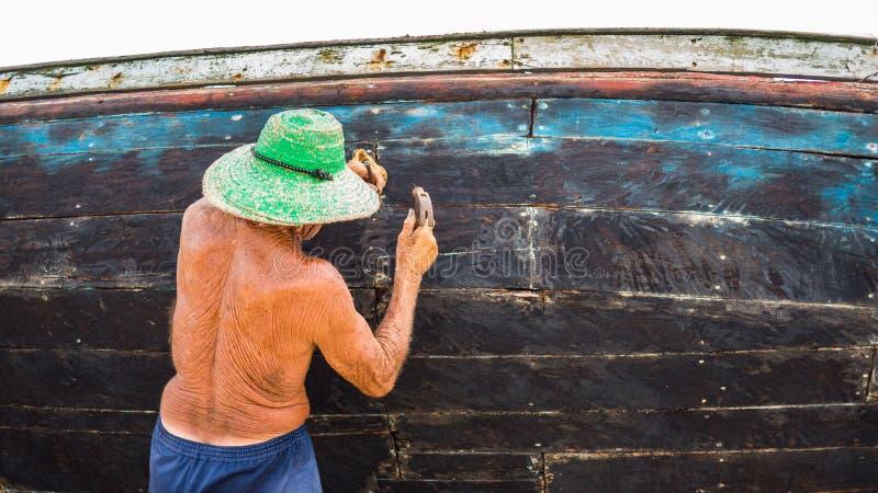 Stary rybak pracuje na jego łodzi fotografia royalty free