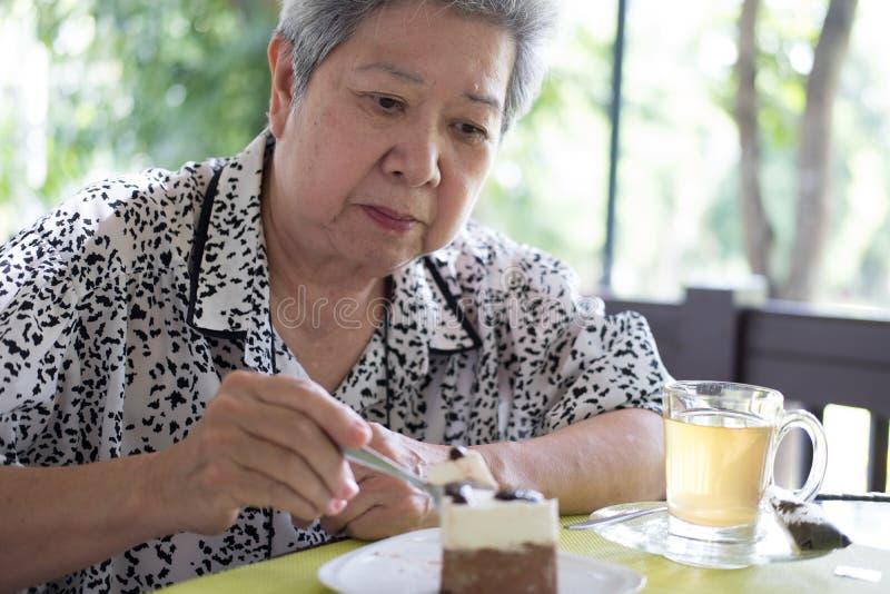 Stary senoir je czekoladowego mousse tort przy kawiarnią starsza kobieta ogniska oko zdjęcie stock