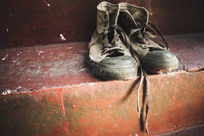 Stary sneakers stojak na czerwień betonie fotografia royalty free