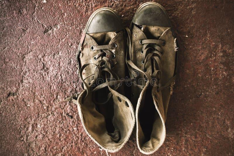 Stary sneakers stojak na czerwonej podłoga obrazy stock