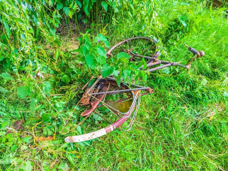 Stary spadać oddzielnie ośniedziały bicykl rzucający daleko od w parku w trawy polu zdjęcia stock