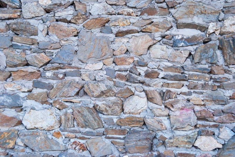 Stary szorstki granitowy kamiennej ściany tekstury tła zbliżenie zdjęcia stock