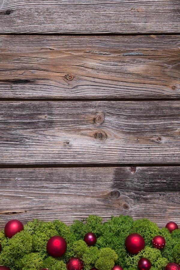 Stary tło drewno z czerwonymi xmas piłkami, mech i obraz stock