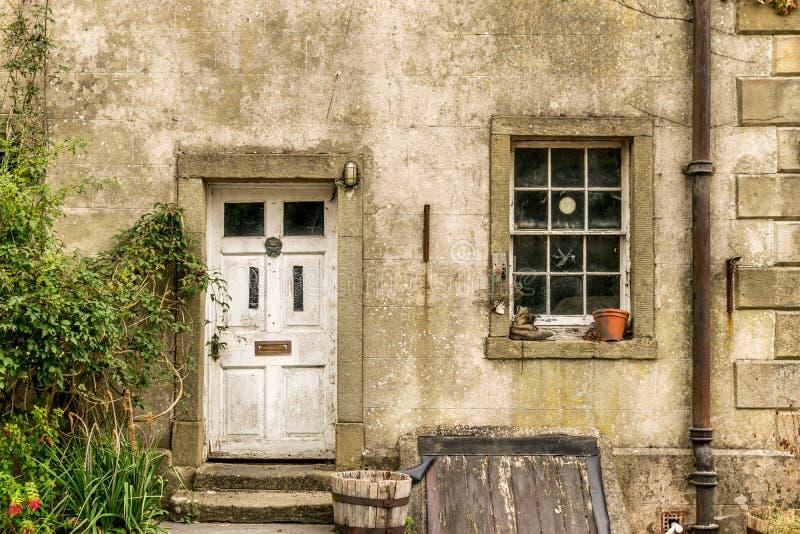 Stary tatty okno z roślina garnkiem butem i, biały drzwi zdjęcia royalty free