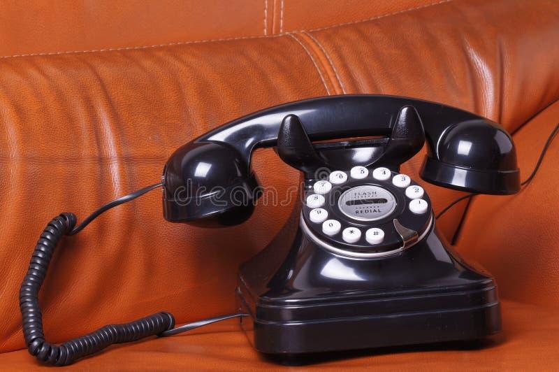 Stary telefon na rzemiennej kanapie obrazy royalty free