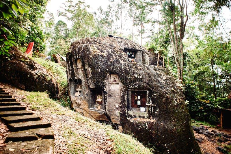 Stary torajan miejsce pochówku w Bori, Taniec Toraja Cmentarz z trumnami umieszczać w ogromnym kamieniu Indonezja, Rantapao, Sula zdjęcie stock