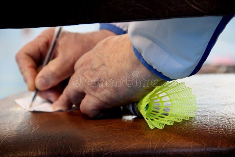 stary trener bierze notatki z shuttlecock dla badminton w jego pięści, obramia w górę obraz stock