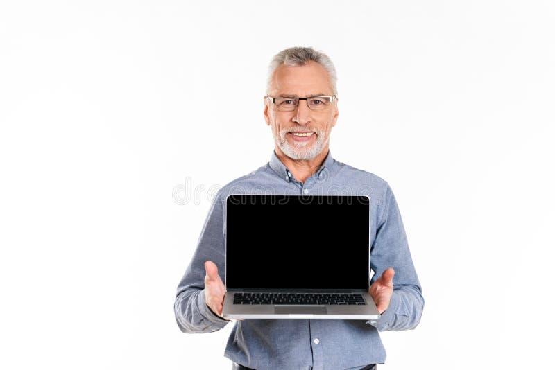 Stary uśmiechnięty mężczyzna pokazuje laptop z pustym ekranem odizolowywającym zdjęcie royalty free