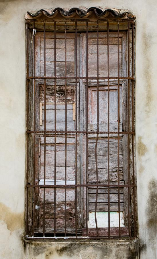 Stary unpainted biel zamyka w okno za rdzewiejącymi stalowymi pręt o obraz stock