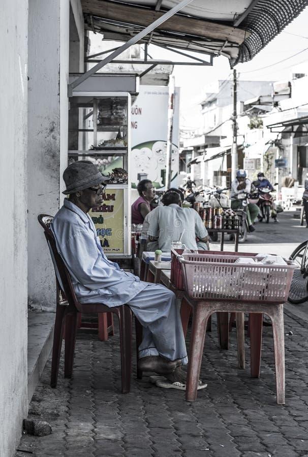 Stary Wietnamski mężczyzna w pyjamas siedzi w ulicie wewnątrz Może Gio, Wietnam zdjęcia stock