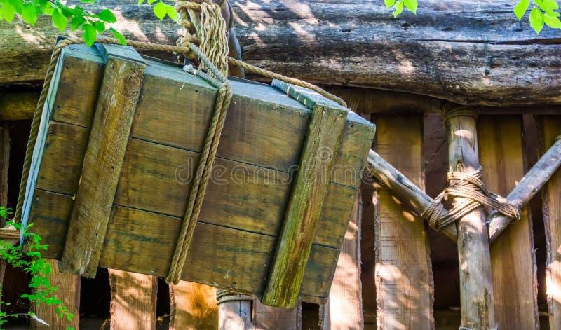 Stary wietrzejący drewnianego pudełka obwieszenie na linowym, średniowiecznym tle, podnośnym metod, wysyłki i schronienia, zdjęcie royalty free