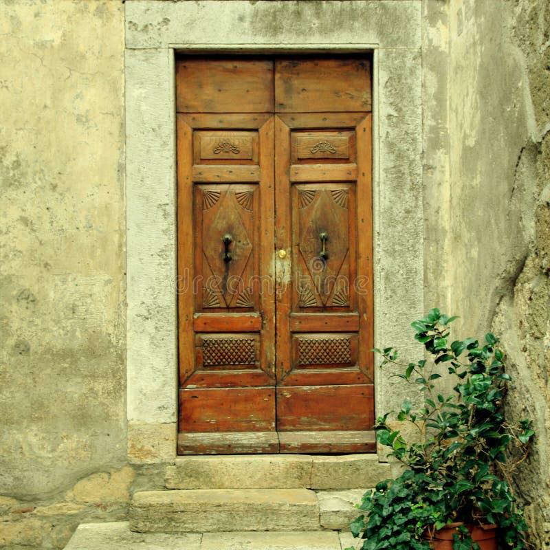 Stary wietrzejący drewniany drzwi wioska dom, Tuscany, Włochy zdjęcie stock