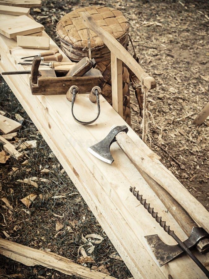 Stary woodworking handtool: drewniany samolot, ścinaka ax i rysować nóż w ciesielka warsztacie na drewnianej ławki ziemi, fotografia stock