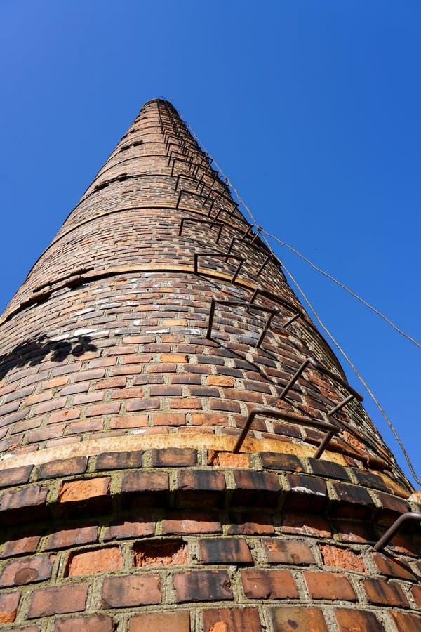 Stary wysoki fabryczny komin przeciw niebieskiemu niebu zdjęcie stock
