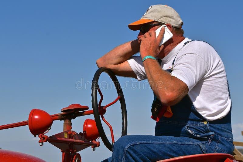 Stary wznawiający ciągnikowy ciągnik i telefonu komórkowego operator zdjęcie royalty free