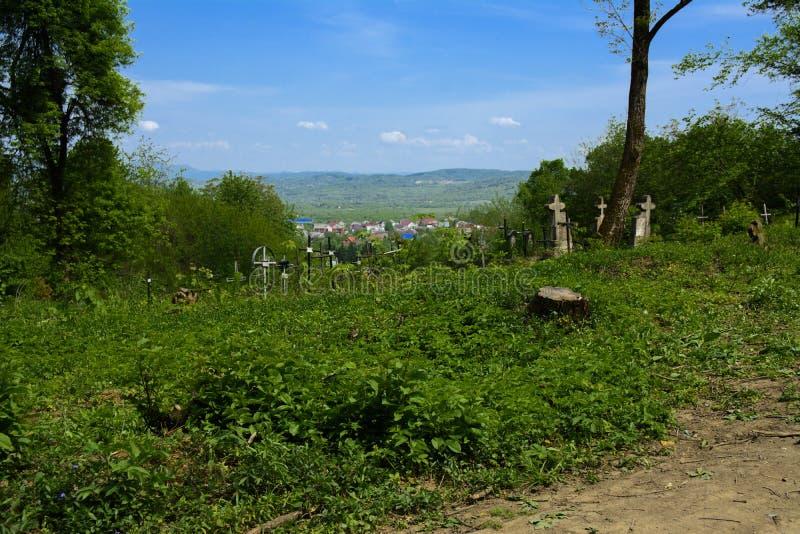 Stary zaniechany cmentarz, krzyże i grób przerastający z tal, zdjęcie stock