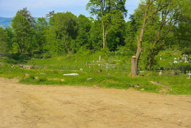 Stary zaniechany cmentarz, krzyże i grób przerastający z tal, zdjęcia stock
