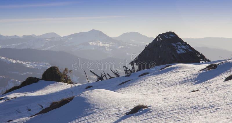 Stary zaniechany dom w śnieżnych górach obraz stock
