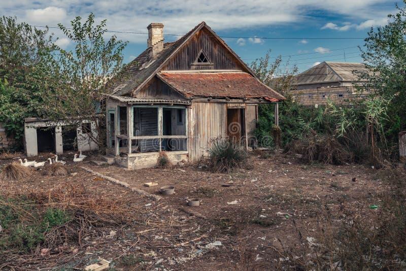 Stary zaniechany drewniany wiejski dom i jard zdjęcia royalty free