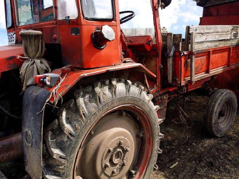 Stary zaniedbany zmrok - czerwony ciągnik z gum brudnymi kołami fotografia stock