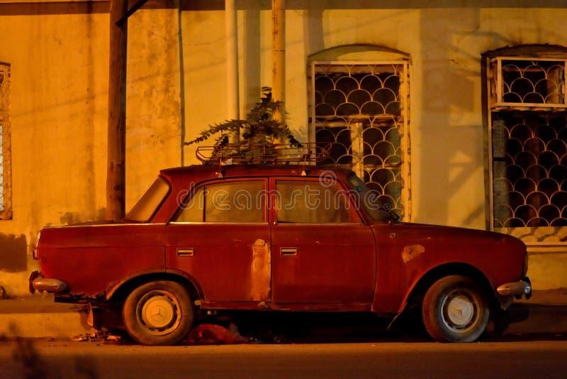 Stary Zhiguli samochód przy nocą pod ulicznym oświetleniem z Mercedez, toczy, w Baku, Azerbejdżan fotografia royalty free