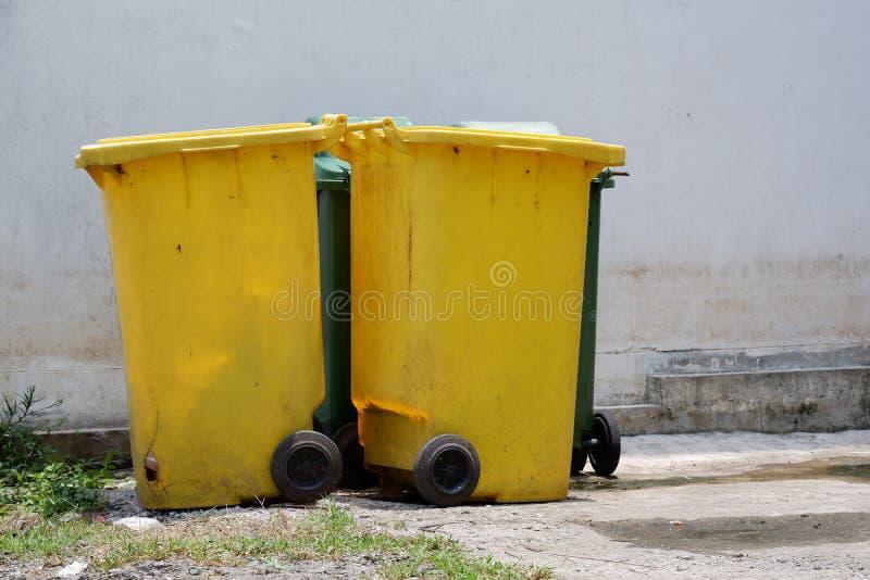Stary zieleni i koloru żółtego kosz na śmieci obrazy stock