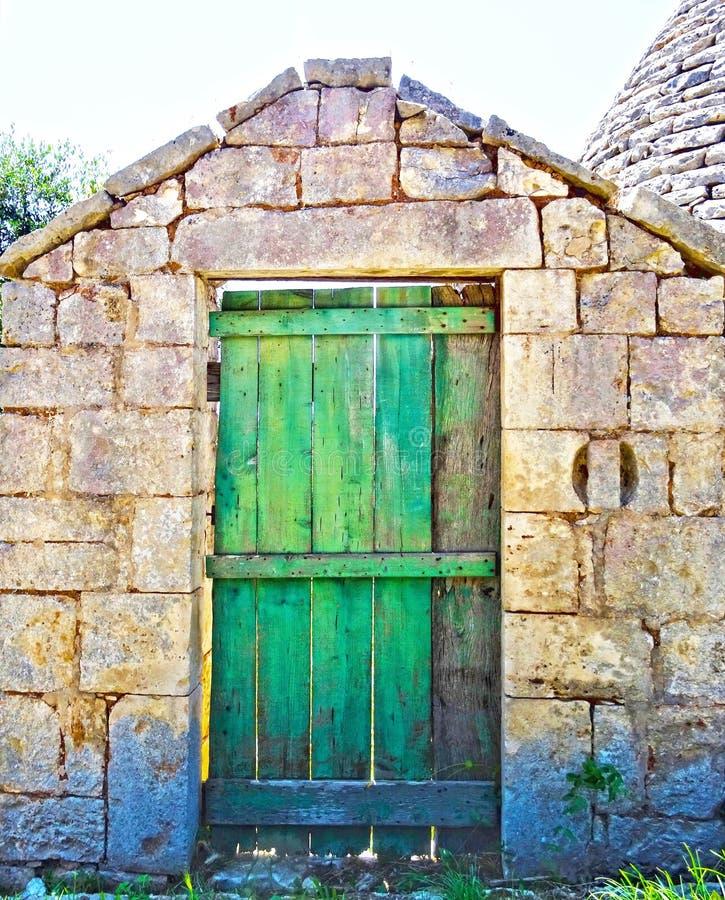 Stary zielony drewniany drzwi na starej kamiennej ścianie zdjęcia royalty free