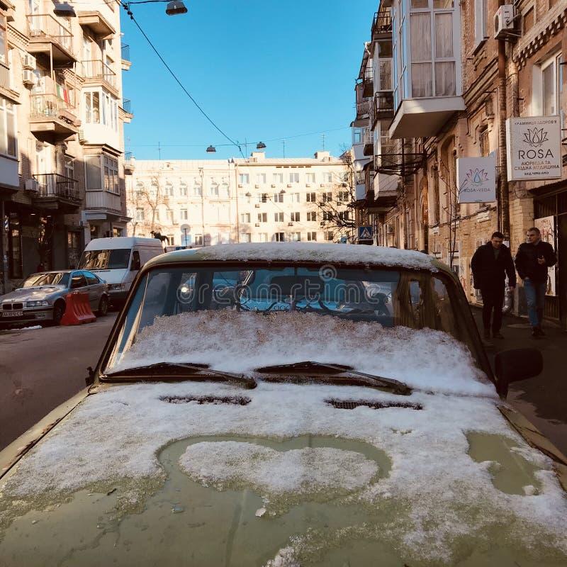 Stary zielony Lada siedzi pod koc śnieg na ulicach Kyiv, UKRAINA, KYIV - obrazy royalty free