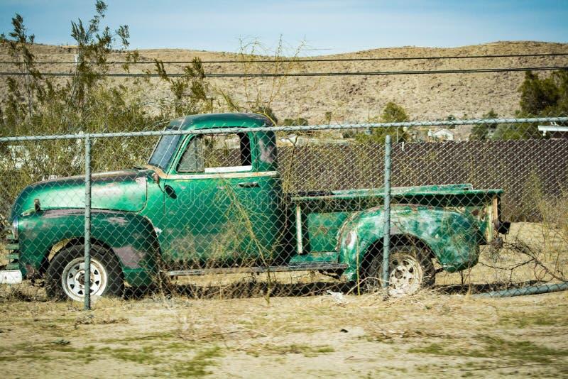 Stary Zielony Pickup za łańcuszkowego połączenia ogrodzeniem obraz royalty free