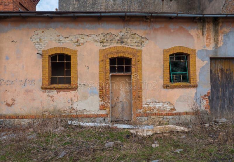 Stary, zniszczony budynek z drzwi, i dwa okno zdjęcie stock