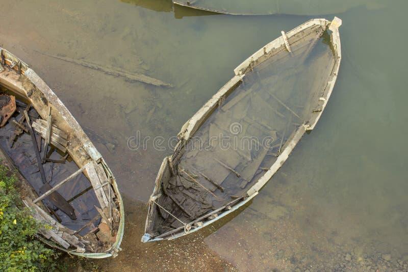 Stary zniszczony i zanurzający w wodzie blisko brzeg łódkowaty odgórny widok obrazy stock