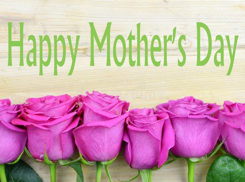 Starzeć się jaskrawych menchii róży płatki tworzy granicę na nieociosanym drewnianym tle dla matka dnia obrazy stock