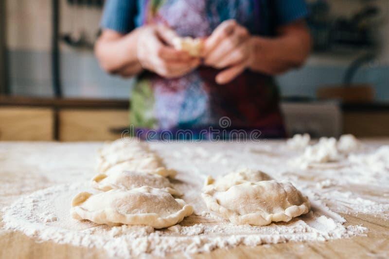 Starzejący się kobiety narządzania ciastka wypełniali z chałupa serem obraz stock