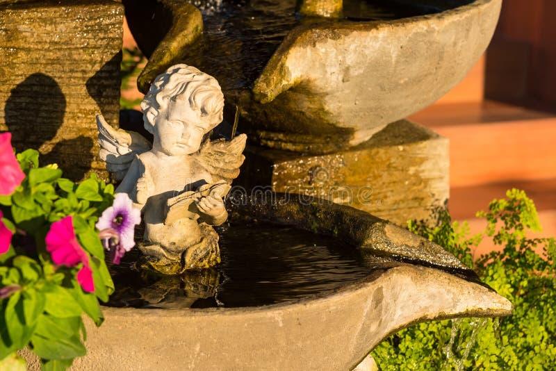 Starzejąca się biała anioła amorka rzeźba siedzi wodną fontannę Tajlandia obrazy stock