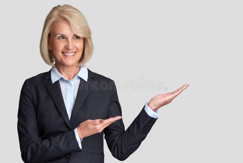 Starzejąca się biznesowa kobieta przedstawia copyspace zdjęcie royalty free