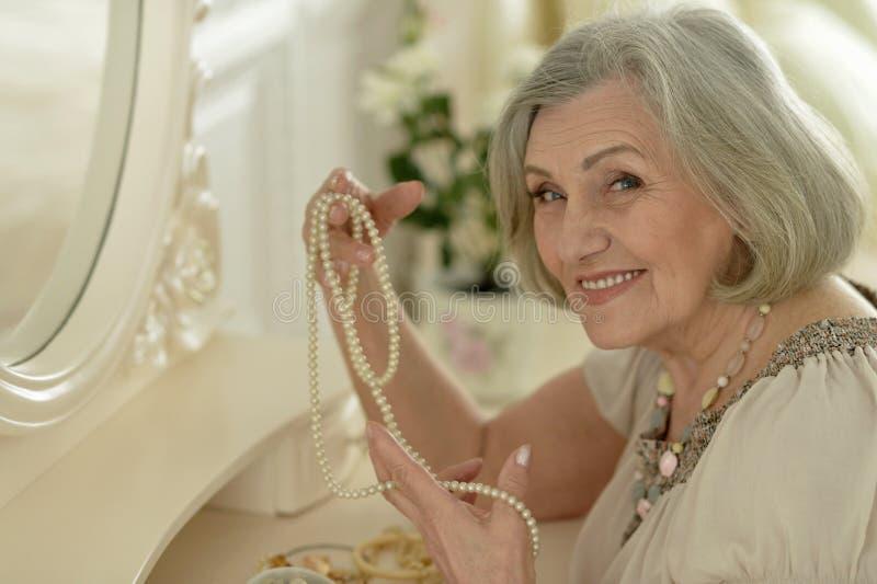 Starzejąca się kobieta blisko lustra zdjęcia royalty free