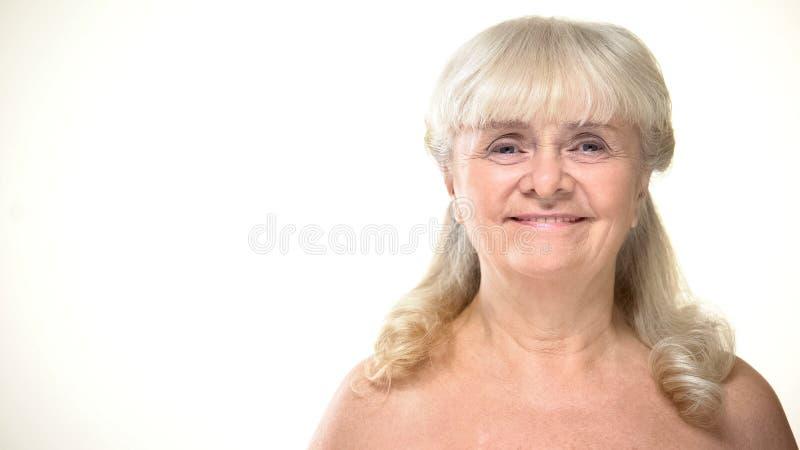 Starzejąca się kobieta ono uśmiecha się na kamerze z nagimi ramionami, bodycare pojęcie, kosmetologia obrazy royalty free