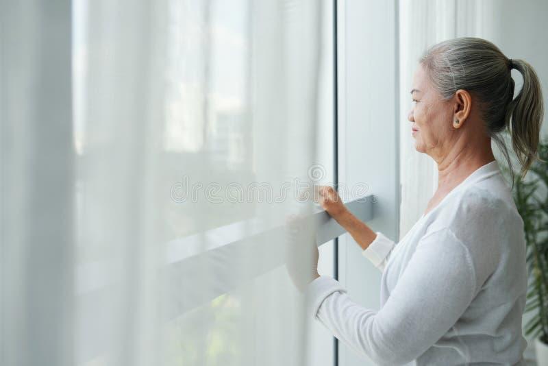 Starzejąca się kobieta patrzeje przez okno zdjęcie royalty free