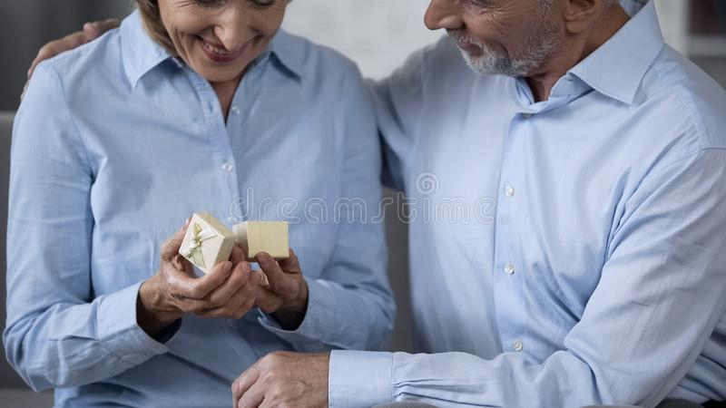 Starzejąca się kobieta uśmiecha się małego teraźniejszości pudełko i trzyma, mężczyzna ściska ona, rocznica zdjęcia royalty free