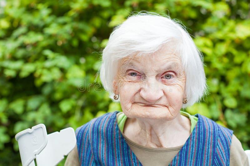 Starzejąca się kobieta w ogródzie zdjęcia stock